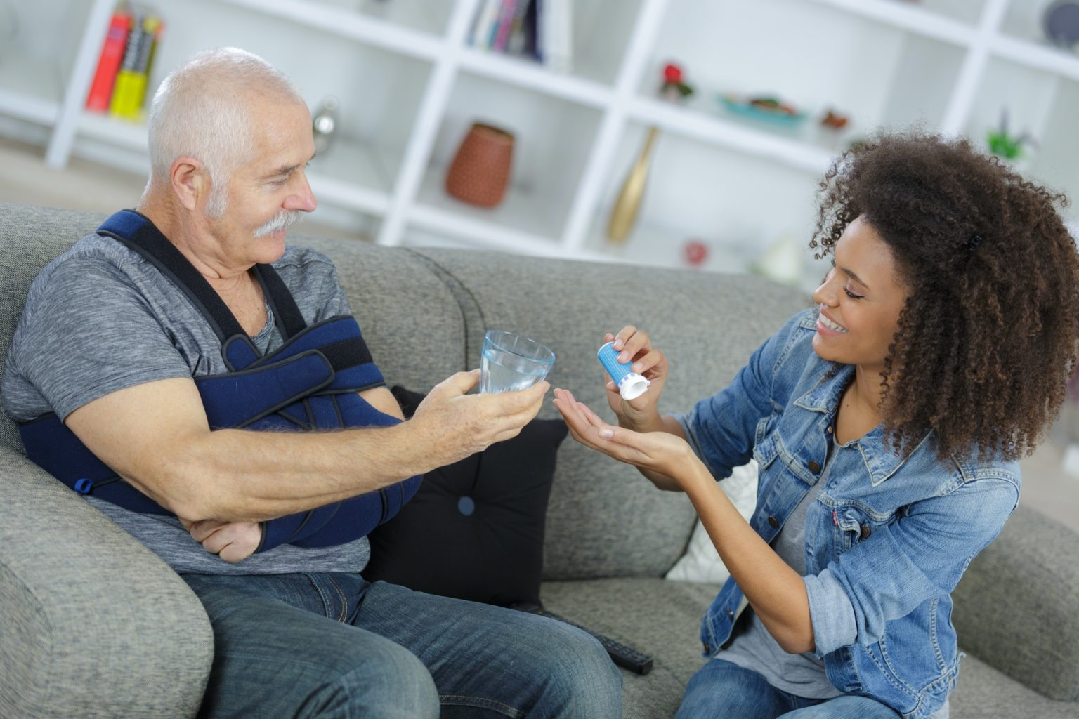 Lady preparing medication for senior man with his arm in a sling