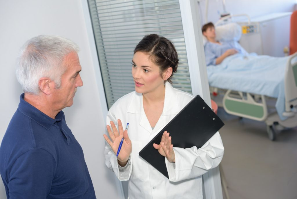 Nurse talking to family member outside of patient's room
