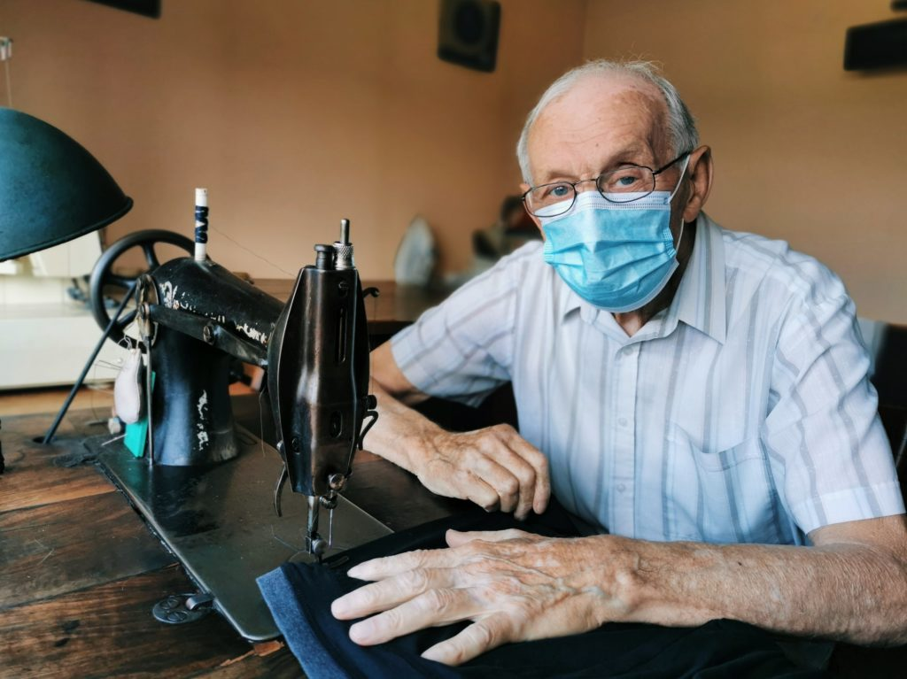 Old tailor wearing a protective surgical mask at home